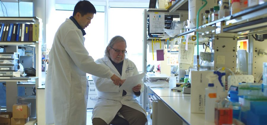 Jim Allison discusses a paper with a research associate in their lab