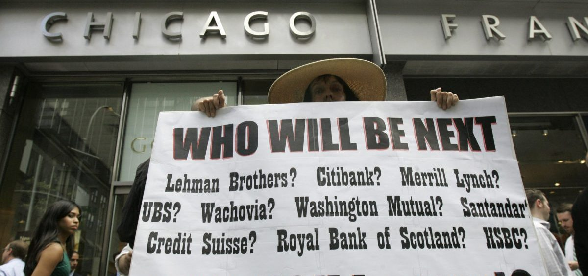 Robin Radaetz holds a sign in front of the Lehman Brothers headquarters on Sept. 15, 2008, in New York. Lehman Brothers filed for Chapter 11 protection in the biggest bankruptcy filing ever at the time and the development was an early part of financial crisis that quickly grew and forced Washington to respond.