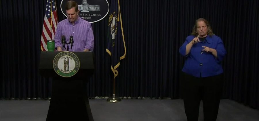 Gov of Kentucky at podium with sign language interpreter next to him