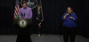 Gov of Kentucky at podium with sign language interpreter next to him