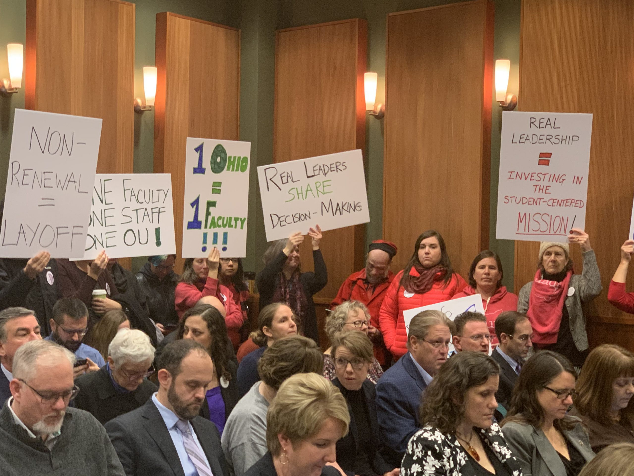 Protestors stand in crowded meeting with signs.