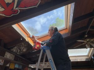 Wayne Barnhart stands on a ladder to touch up paint on one of the skylights at the Smiling Skull Saloon on Thursday, May 14, 2020.