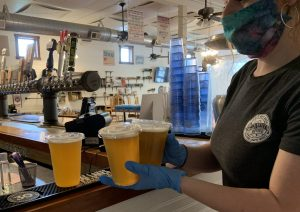 Ashton Wise collects three cups of beer to carry out to the patio at Eclipse Company Store on Friday, May 15, 2020.