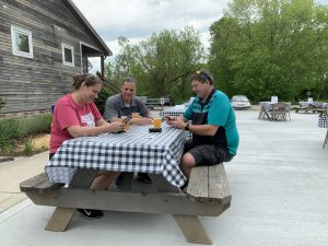 From left: Wendy Kaaz, Jeff Kaaz, and Bruce Steenrod sit in the beer garden at Eclipse Company Store in The Plains, Ohio, on May 15, 2020.