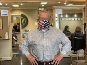 Fritz Bookman poses inside G.F. Bookman & Co. Attitudes, the salon he owns and operates in Nelsonville, Ohio, on May 19, 2020. He is wearing a face mask with the American flag on it as employees cut clients' hair in the background.