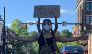 """Brooklyn Stallworth stands on Court Street with her arms wide, as Kel Davis stands behind her. Stallworth has """"black skin is not a threat"""" written on her inner forearms. The sign behind her says """"black lives matter."""""""