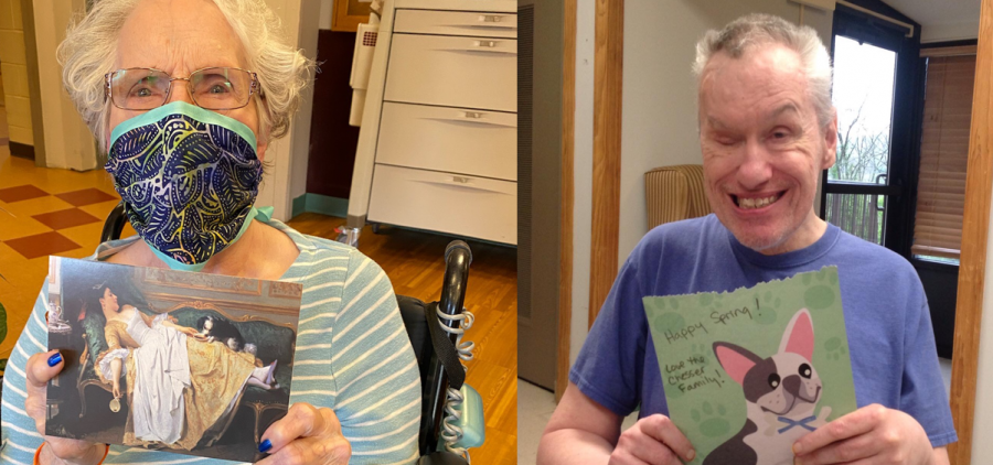 Two residents of a nursing home hold up cards they received from a community mail program