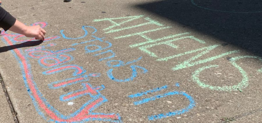"Mary Nally writes ""Athens Stands in Solidarity"" with chalk on the sidewalk outside of the Athens County Courthouse on Sunday, May 31, 2020."