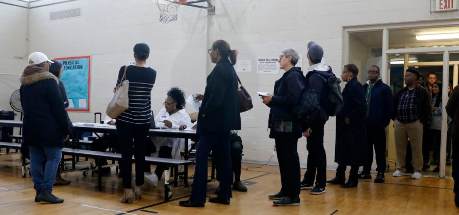 People stand in line at a Detroit polling place during Michigan's March 10 presidential primary. Because of the pandemic, the state's top election official is sending absentee ballot applications to every registered voter for the fall election.