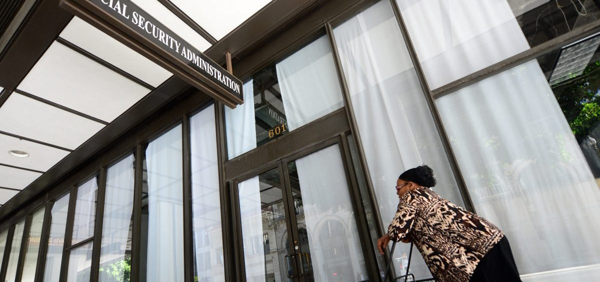 A woman passes a closed Social Security Administration office in Los Angeles in 2013. Some 53,000 of the agency's workers are now working from home.