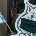 A cardboard cutout of Rufus Bobcat wearing a mask outside of College Bookstore in uptown Athens.