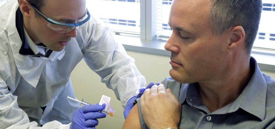 """Pharmacist Michael Witte (left) gives Neal Browning a shot in the first-stage study of a potential coronavirus vaccine on March 16 in Seattle. Countries and companies are racing to find a vaccine with some describing the competition as """"vaccine nationalism."""""""