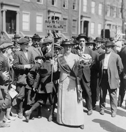 """Suffragist, """"Mrs. Suffern,"""" holding sign; crowd of boys and men behind. New York, 1914."""