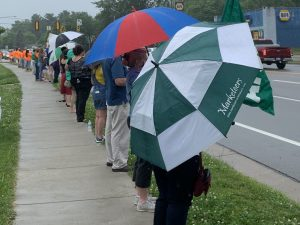 A line of people with signs and umbrellas express their support for Ohio University employees whose positions have been abolished.