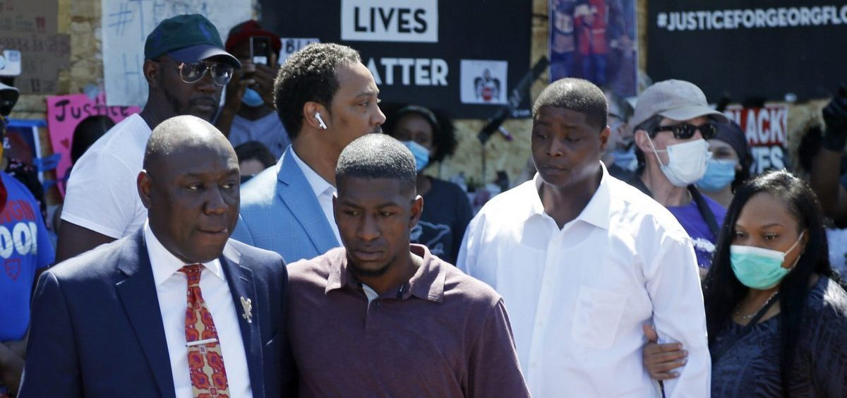 All four former Minneapolis police officers now face criminal charges in the death of George Floyd. Attorney Ben Crump, left, escorts Floyd's son Quincy Mason, second from left, on Wednesday during a visit to the memorial where Floyd was arrested in Minneapolis.