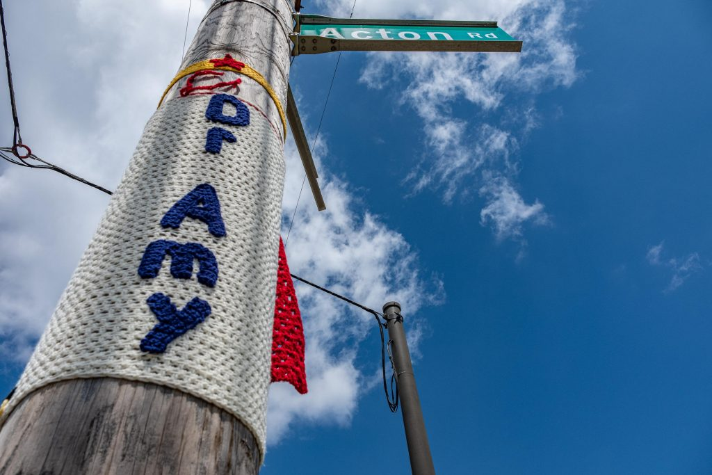 """A """"yarn bomber"""" created a sign for Acton Road in Clintonville that says """"Dr Amy."""""""