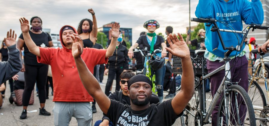 Demonstrators kneel and raise their hands during a protest in Minneapolis on Sunday.