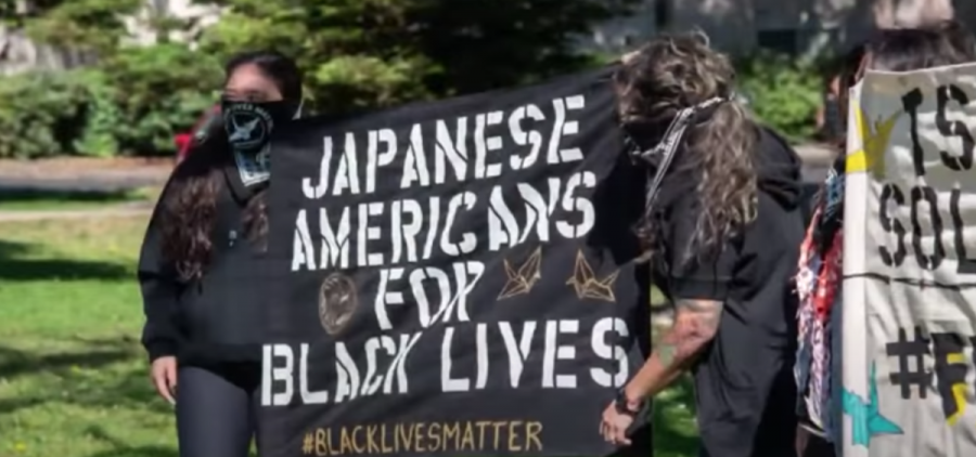 two protestors holding sign that says Japanese Americans for Black Lives