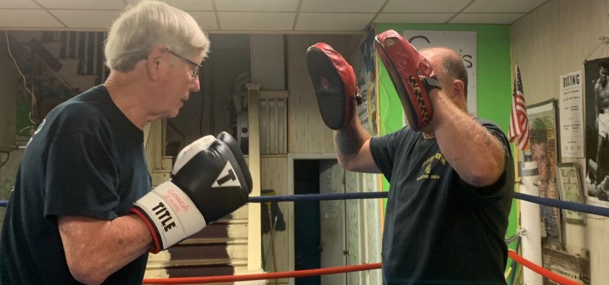 Sam Jones, left, demonstrates some boxing stances and combinations with Rob Robinson at Sam's Gym in Glouster, Ohio, on Wednesday, June 10, 2020.