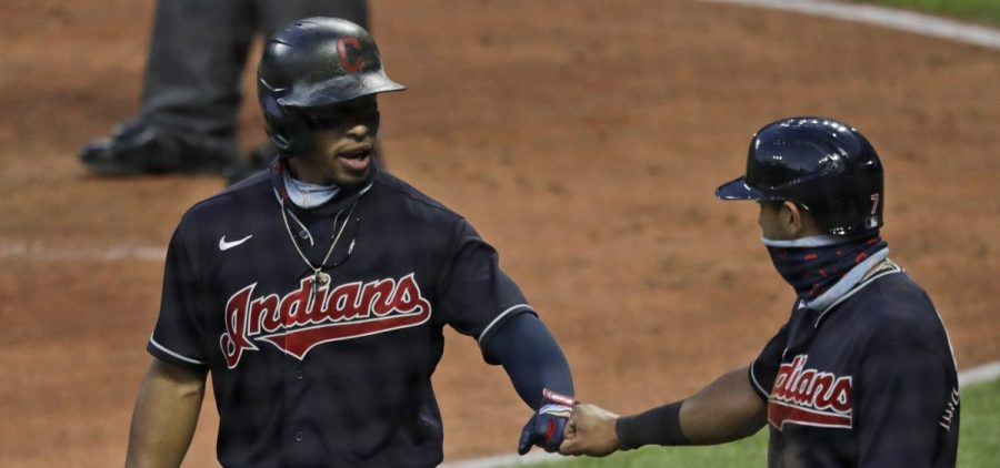 Cleveland Indians' Francisco Lindor, left, is congratulated by Cesar Hernandez after hitting a three-run home run in the fifth inning during a preseason baseball game against the Pittsburgh Pirates, Monday, July 20, 2020, in Cleveland.