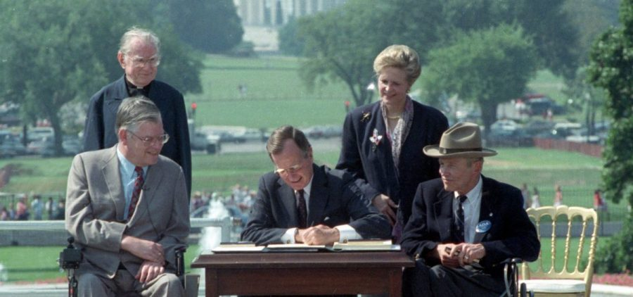 In this July 26, 1990 file photo, President George H. W. Bush signs the Americans with Disabilities Act during a ceremony on the South Lawn of the White House. Joining the president are, from left, Evan Kemp, chairman of the Equal Opportunity Employment Commission; Rev. Harold Wilke; Sandra Parrino, chairman of the National Council on Disability, and Justin Dart, chairman of The President's Council on Disabilities. TheAmericans with Disabilities Act, which was signed into law 25 years ago, on July 26, 1990.