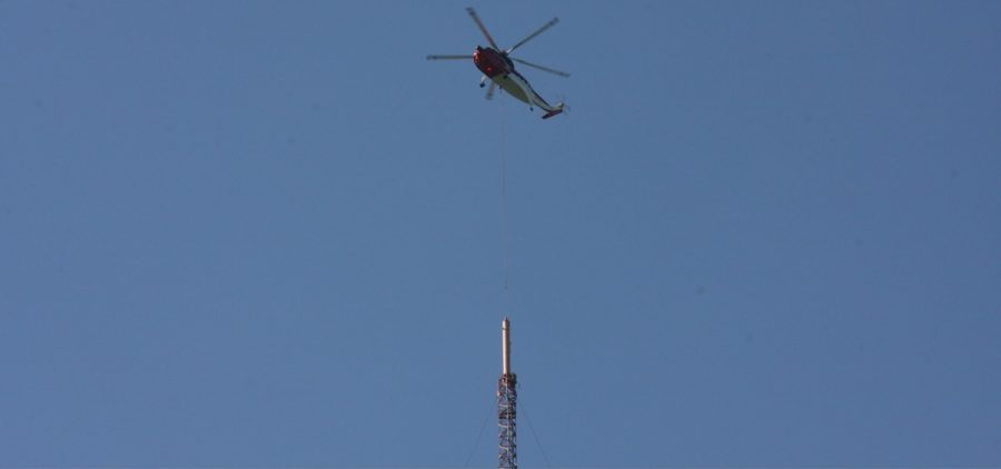 Helicopter hovering above old antenna