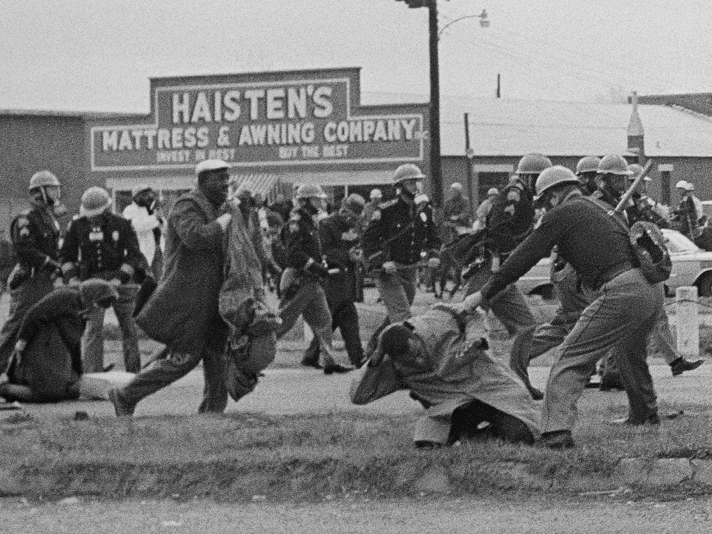State troopers swing billy clubs at protesters, including John Lewis in the foreground, at a civil rights voting march in Selma, Ala., on March 7, 1965, that became known as Bloody Sunday.