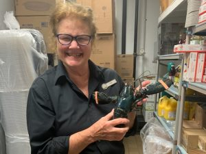 Red Lobster employee Lora Jones holds her special discovery. The blue lobster now lives at the Akron Zoo.