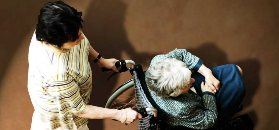 Nurse assists a nursing home resident in a wheelchair
