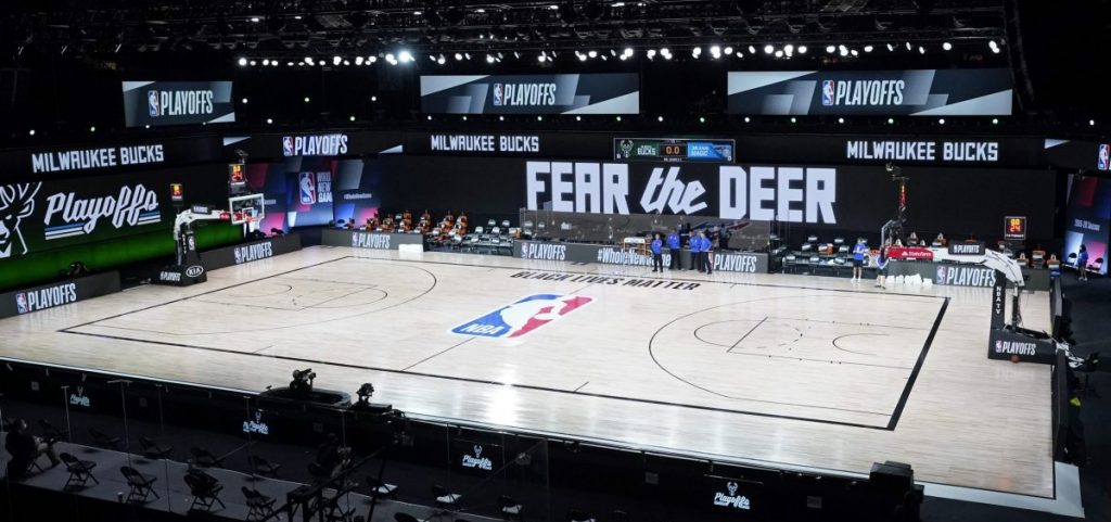 Officials stand beside an empty court at the scheduled start of an NBA basketball first round playoff game between the Milwaukee Bucks and the Orlando Magic, Wednesday, Aug. 26, 2020, in Lake Buena Vista, Fla.