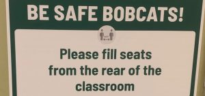 A sign inside one of Ohio University's academic buildings encouraging students to fill seats from the back of the room