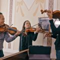 Three violinists playing