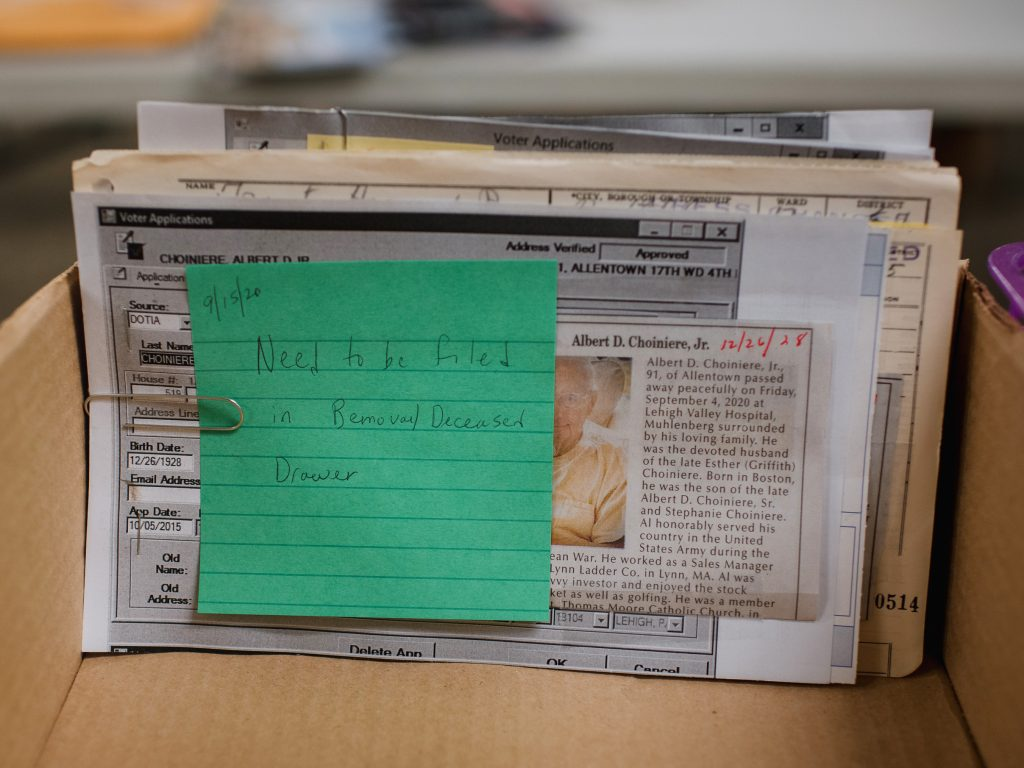 """A memo stating """"Need to be filed in Removal/Deceased Drawer"""" is attached to an obituary newspaper clipping. Election workers check obituaries to make sure ballots are not sent to people who have died."""
