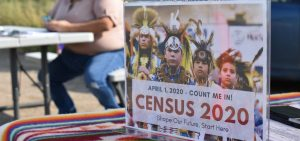 A sign promoting participation in the 2020 census is displayed as Selena Rides Horse enters information into a phone for a member of the Crow Indian Tribe in Lodge Grass, Mont., in August.