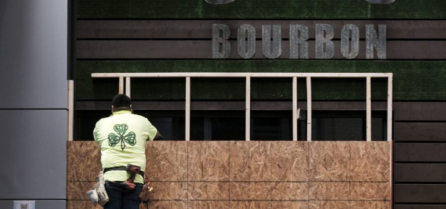 A worker boards up a business in downtown Louisville on Tuesday in anticipation of the results of a grand jury inquiry into the death of Breonna Taylor.