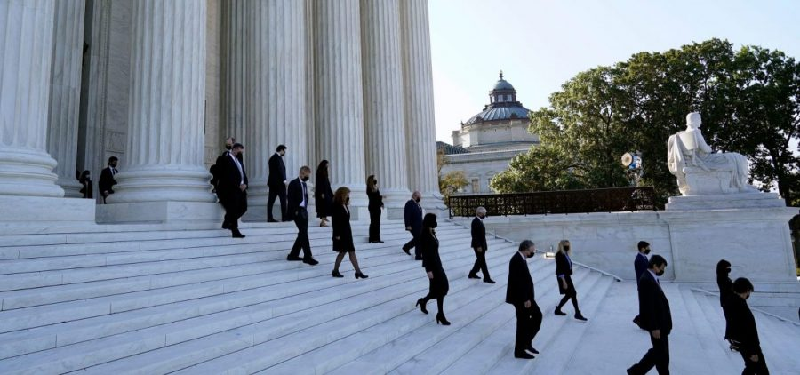 Former law clerks for Justice Ruth Bader Ginsburg stand on the steps of the Supreme Court as they await the arrival of the casket of Ginsburg on Wednesday.