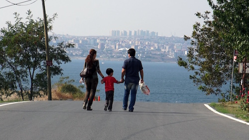 Couple with child between them walking down street
