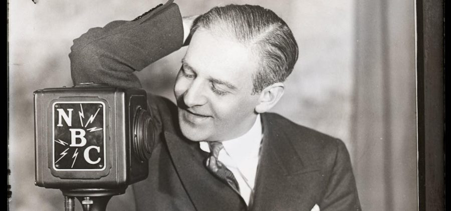 Young Winchell playfully leans against an NBC microphone.