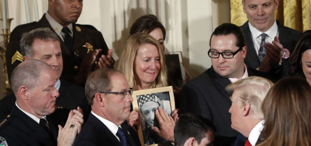 In this Oct. 26, 2017, file photo, Jeanne Moser, center, of East Kingston, N.H., watches as President Donald Trump reaches out to touch a photo of her son, Adam Moser, during an event to declare the opioid crisis a national public health emergency in the East Room of the White House in Washington. Adam was 27 when he died from an apparent fentanyl overdose. The coronavirus outbreak and the Trump administration's response to the pandemic have been a dominating theme in this year's presidential race.