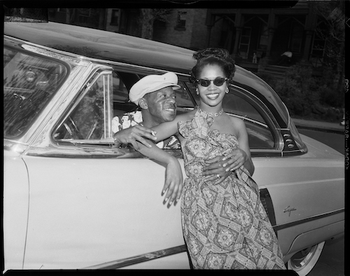 Woman posed against 1952 Lincoln Capri coupe car, with man leaning out of driver's side and wrapping his arms around her, Pittsburgh, Pennsylvania, c. 1952 - 1960.