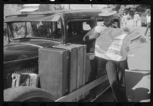 1940's Black man looking over road map