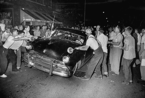A crowd attacking cars driven by African Americans to protest integration in the schools.