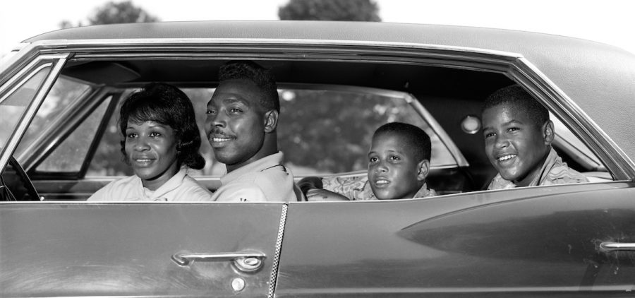 1960s SIDE VIEW OUTDOOR SMILING AFRICAN AMERICAN FAMILY FATHER MOTHER TWO SONS SITTING IN FOUR DOOR SEDAN AUTOMOBILE (Photo by H. Armstrong Roberts/ClassicStock/Getty Images)