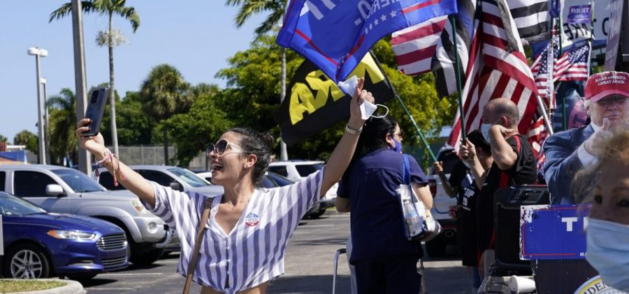 Juliet Roa takes a selfie as supporters of President Trump wave flags outside an early voting location at the John F. Kennedy Library on Tuesday in Hialeah, Fla.