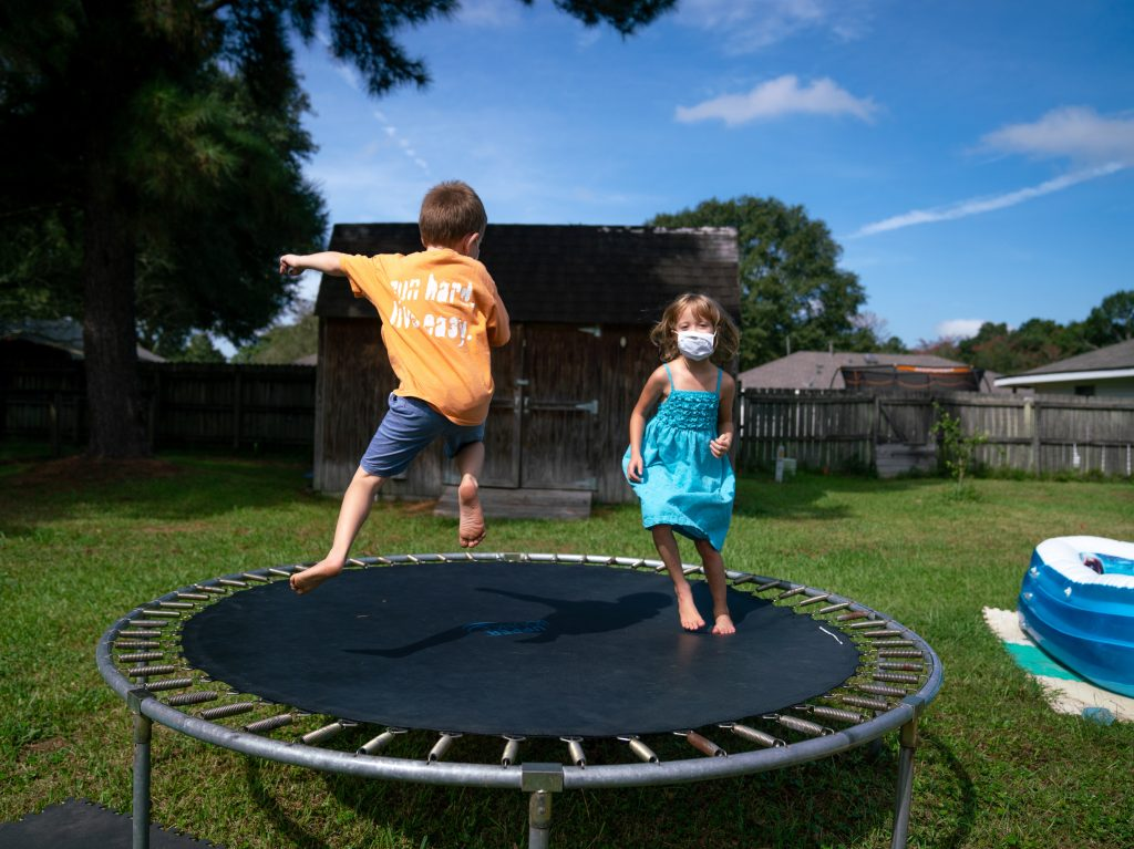 Lachlan (left) and Lillian Barilleau play in the backyard of their home in Central, La. They were displaced from the house for months after a flood in 2016.