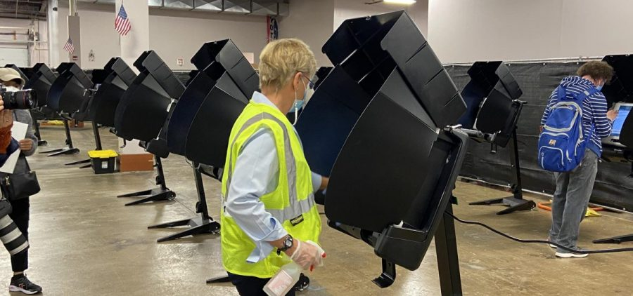 A poll worker disinfecting a voting machine.