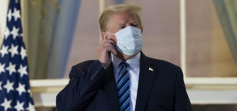 President Donald Trump removes his mask as he stands on the Blue Room Balcony upon returning to the White House Monday, Oct. 5, 2020, in Washington, after leaving Walter Reed National Military Medical Center, in Bethesda, Md. Trump announced he tested positive for COVID-19 on Oct. 2.