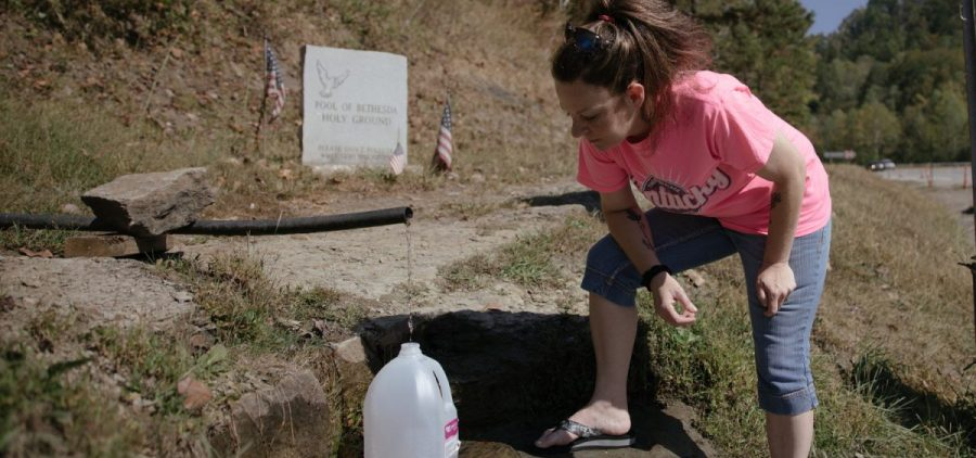 BarbiAnn Maynard drives 45 minutes from her home in Martin County, Kentucky, to a spring at the Mingo-Logan county line in West Virginia to fill containers with fresh water.