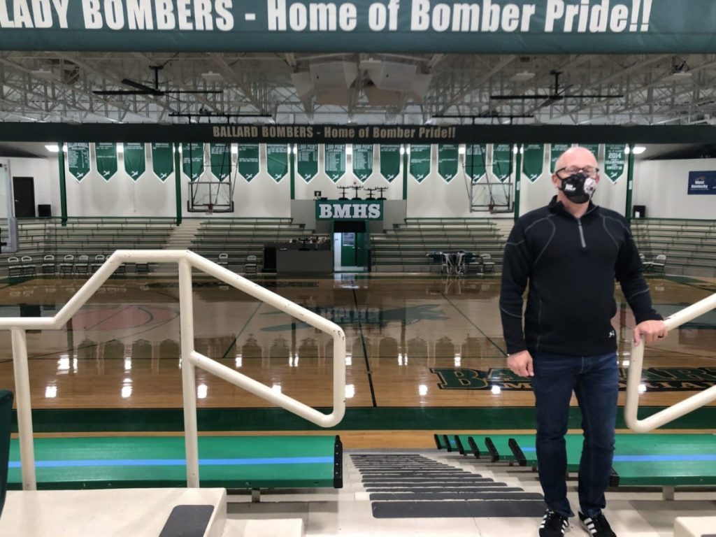 """David Meinschein stands in front of the Ballard Memorial High School basketball gym, known as the """"Green Palace""""."""