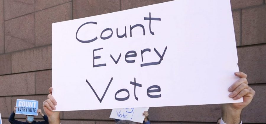 Demonstrators stand across the street from the federal courthouse in Houston, Monday, Nov. 2, 2020, before a hearing in federal court involving drive-thru ballots cast in Harris County.
